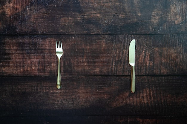 Old wooden table with fork and knife waiting for a dish of missing food