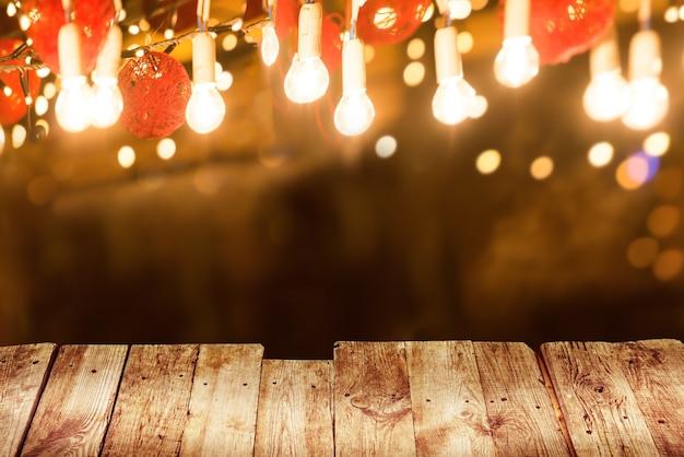 夜の街の通りで電球の照明と古い木製のテーブル