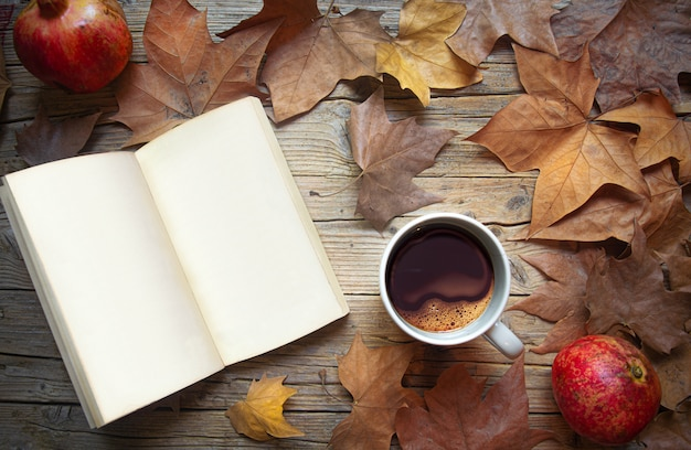 Old wooden table with open book and blank pages dry autumn leaves and cup of coffee