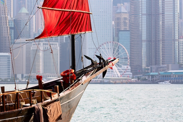 Old wooden tourist junk ferry boat in victoria harbor and famous hong kong island view with observation wheel.
