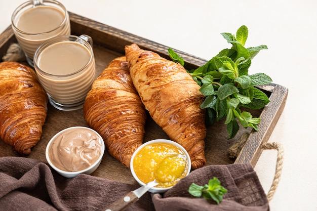 サクサクのクロワッサン、ジャム、チョコレートクリーム、コーヒーが入った古い木製トレイ