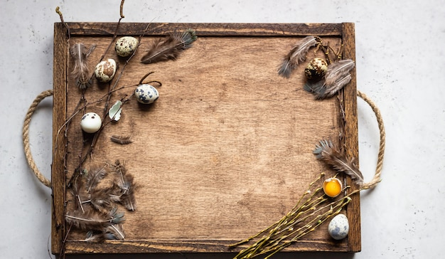 Old wooden tray with quail eggs, willow twigs and feathers