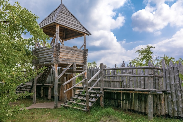 An old wooden watchtower and a palisade made of logs protection of an ancient russian village