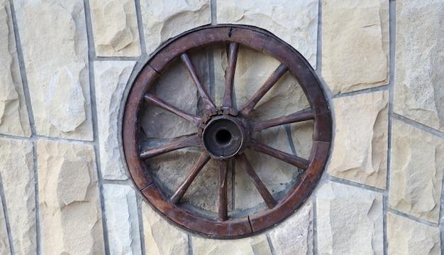 Старое деревянное колесо от телеги на каменной стене сельского дома.