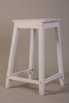 Old wooden white stool on gray
