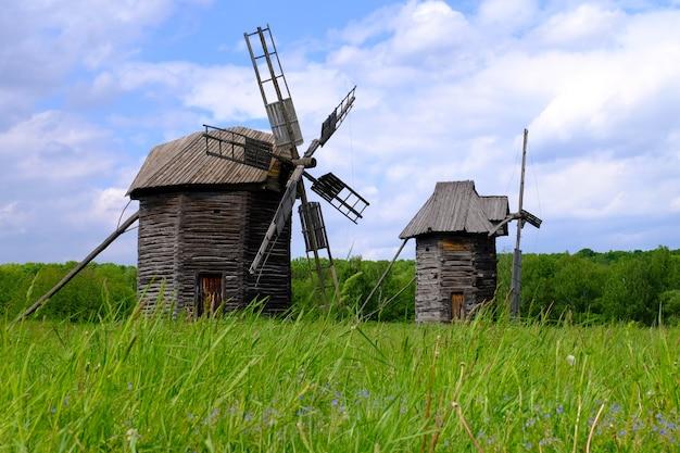 Old wooden windmills on green field, on blue sky