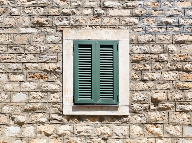 Старое деревянное окно в каменной стене