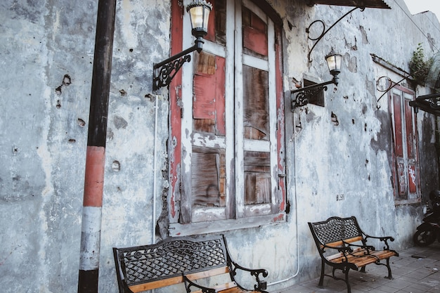 Старые деревянные окна со старинной люстрой на стенах и деревянной скамейкой на земле