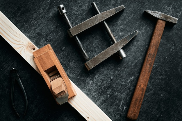 Old woodworking tools on dark background, top view