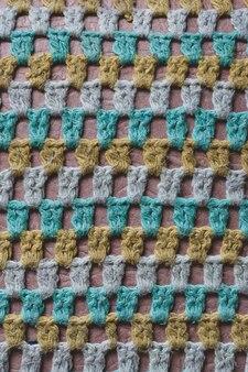 Старое шерстяное трикотажное полотно в сетку. зеленые, белые, желтые нити. текстура глубоких отверстий. вязаный чехол на стул. вертикальный.