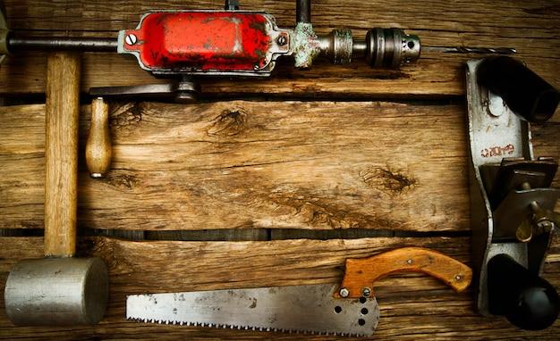 古い作業ツール。木製の背景にヴィンテージの作業ツール(ドリル、のこぎり、定規など)。