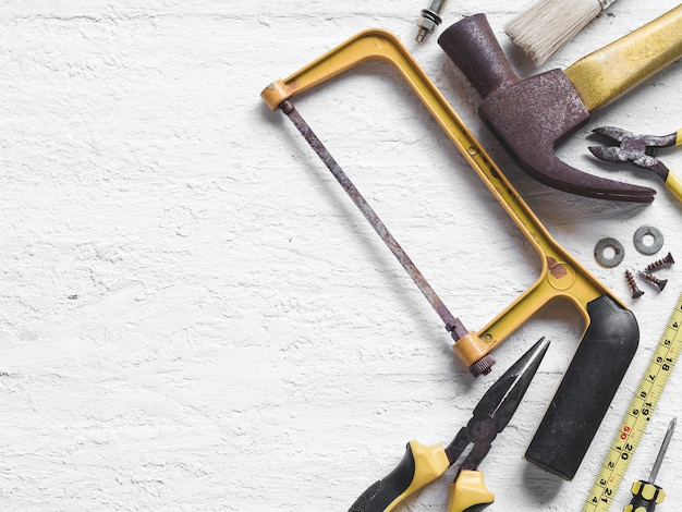Old working tools on wooden background.