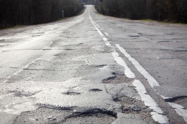 겨울철이 지나면 도로나 고속도로의 오래된 아스팔트 표면. 구덩이와 구멍이 있는 나쁜 길