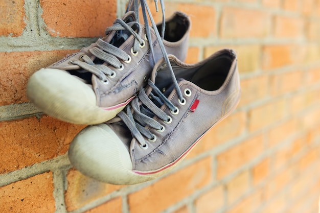 Old worn sneakers on brick wall