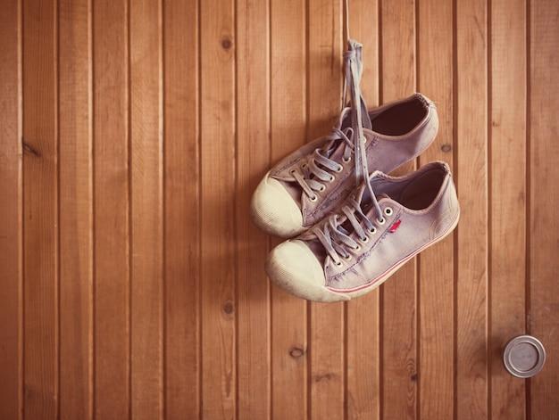 Old worn sneakers on wood