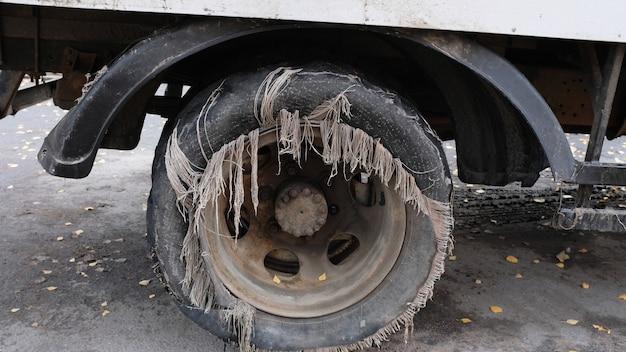 Старая изношенная шина на автомобиле, стоящем на городской улице