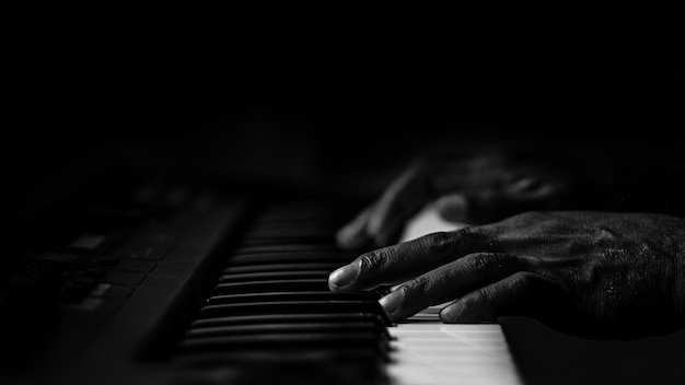 Old wrinkled hands on a piano