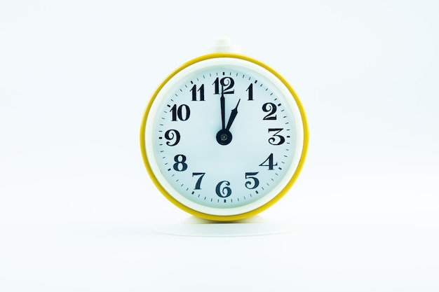 Old yellow alarm clock shows the time 13 o'clock on a white background