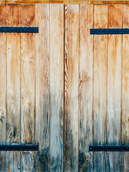 古い黄褐色の赤いドアの木の質感