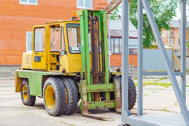 Old yellow forklift truck on the loading area