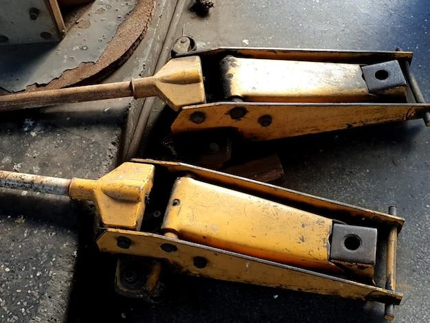 ガレージの古い黄色の油圧フロアジャッキ