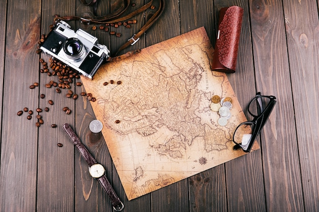 Old yellow map, glasses, coins, leather case, camera, watch, coffee beans and other spices lie on wooden floor