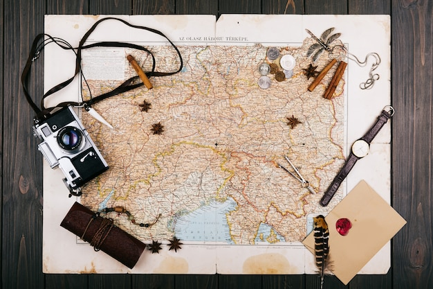 Old yellow map, glasses, coins, leather case, camera, watch, compasses, coffee beans, other spices and cookies lie on wooden floor