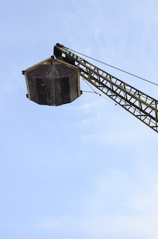 Old yellow mechanical clamshell grab on blue sky background