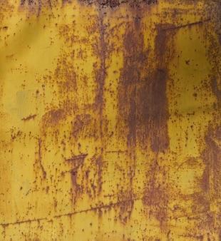 錆びた質感の古い黄色の塗られた壁。グランジ錆びた金属の背景。さび汚れ