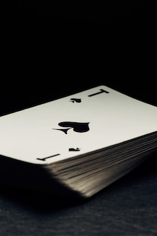 Old yellowed deck of cards on black background. ace of spades lies on top.