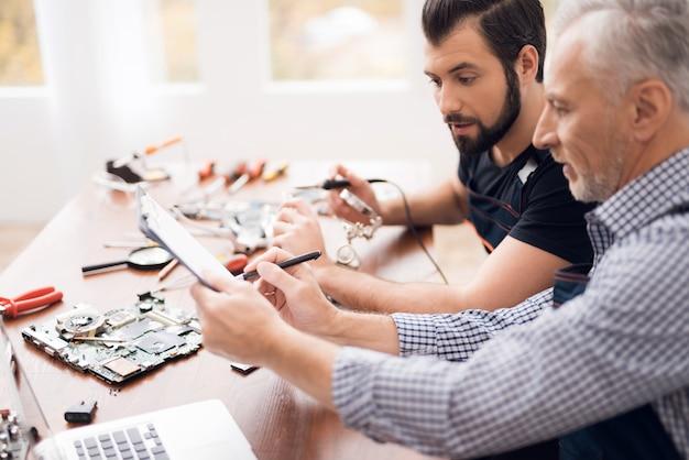 Old and young engineers repair broken motherboard.