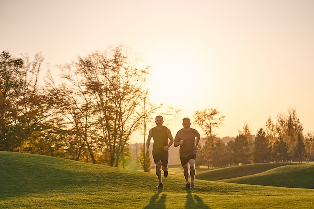 The old and young sportsmen running in the beautiful park