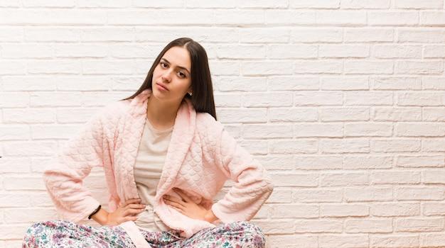 非常に怒っている誰かをoldるパジャマを着た若い女性