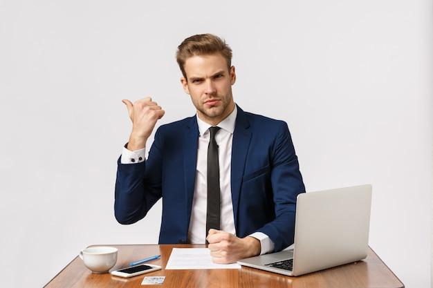 今すぐオフィスを出ましょう。真面目そうな厳格で偉そうな若い男、悪い報告をするold責する従業員、出口を指して不満を訴える、ラップトップとドキュメントで座っているオフィス