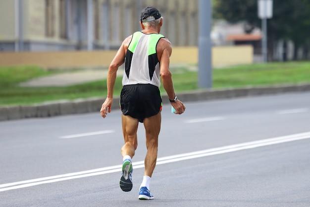 나이든 운동 선수는 마라톤을 실행합니다. 스포츠와 건강