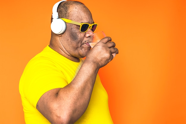 Older black man drinking a glass of cold water listening to music on his headphones and with sunglasses on his face.