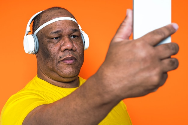 Older black man is with his smartphone making a self portrait and listening to music on his headphones