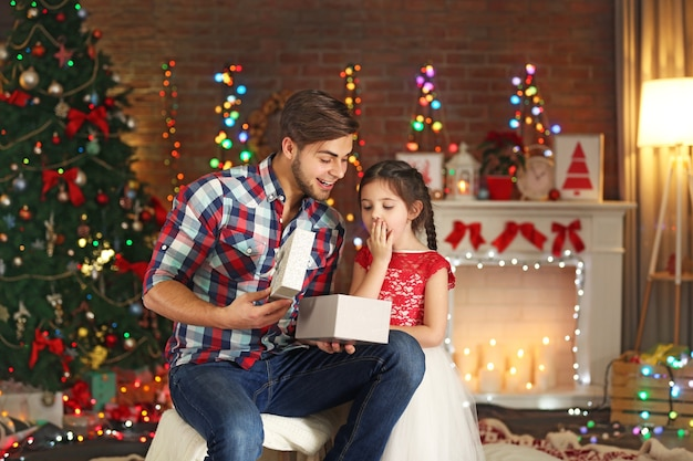 クリスマスのリビングルームで兄と妹のオープニングギフト