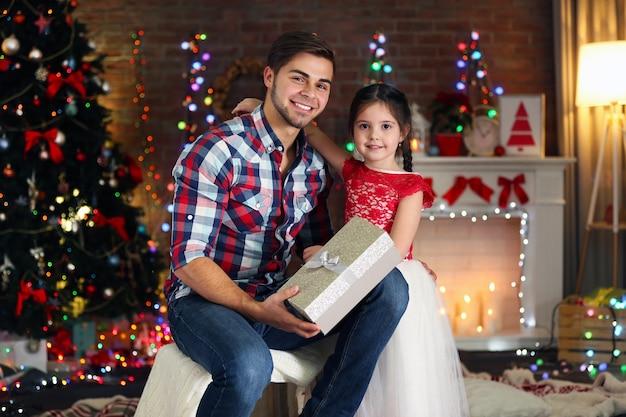 크리스마스 거실에 선물을 들고 앉아 있는 형과 여동생