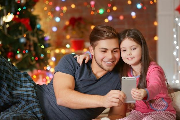 Старший брат и младшая сестра фотографируют себя со смартфоном в рождественской гостиной