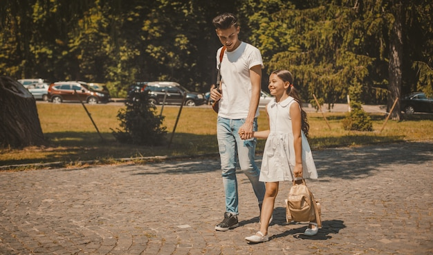 Старший брат и младшая сестра гуляют по улице города