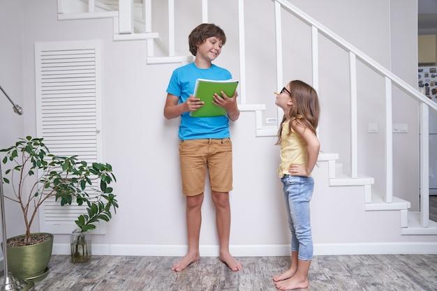 家の階段の近くに立っているかわいい妹の宿題を手伝っている兄