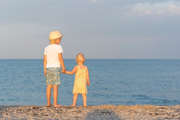 Older brother holds the little sister by the hand and looks at the sea