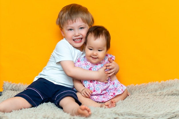 Older brother hugging his little sister. children in on a yellow background