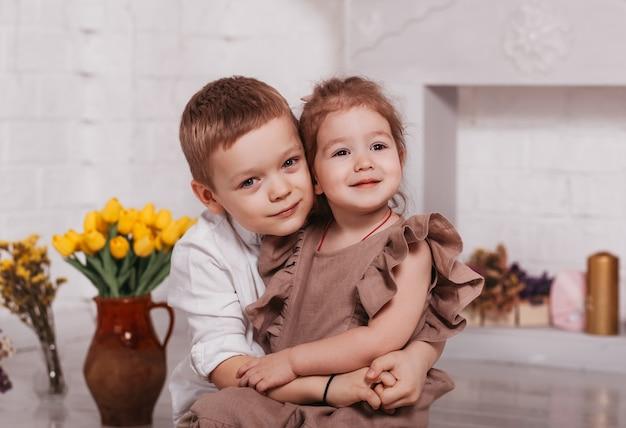 Старший брат обнимает свою младшую сестру в комнате с цветами