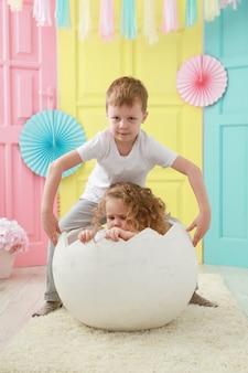 弟が孵化した白い卵に座っている妹の世話をする