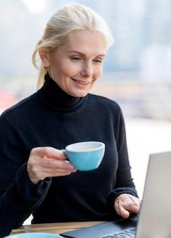 Пожилая деловая женщина, наслаждаясь кофе на открытом воздухе во время работы на ноутбуке