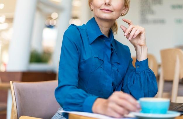 Пожилая деловая женщина пьет кофе во время работы