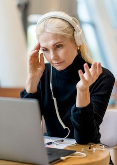 Older business woman having a video call on laptop with headphones