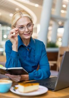 議題を押しながらラップトップを見て眼鏡の古いビジネス女性